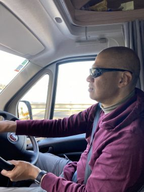 activities for patients and caregivers | FAP News Today | Jaime's husband, Aubrey, wears sunglasses and a maroon sweatshirt while driving the car.